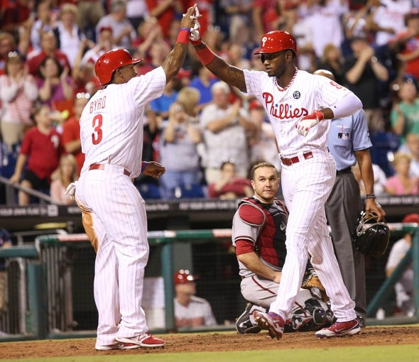 Jul 25, 2014; Philadelphia, PA, USA; Philadelphia Phillies left fielder Domonic Brown (9) is congratulated by right fielder Marlon Byrd (3) after hitting a two RBI home run during the seventh inning of a game against the Arizona Diamondbacks at Citizens Bank Park. The Phillies won 9-5. Mandatory Credit: Bill Streicher-USA TODAY Sports