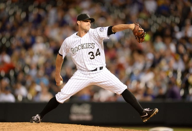 Jul 25, 2014; Denver, CO, USA; Colorado Rockies relief pitcher Matt Belisle (34) delivers a pitch in the ninth inning against the Pittsburgh Pirates at Coors Field. Mandatory Credit: Ron Chenoy-USA TODAY Sports