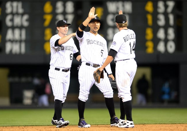 Jul 25, 2014; Denver, CO, USA; Colorado Rockies left fielder Carlos Gonzalez (5) and left fielder Corey Dickerson (6) and second baseman Josh Rutledge (14) react to the win over the Pittsburgh Pirates at Coors Field. The Rockies defeated the Pirates 8-1. Mandatory Credit: Ron Chenoy-USA TODAY Sports