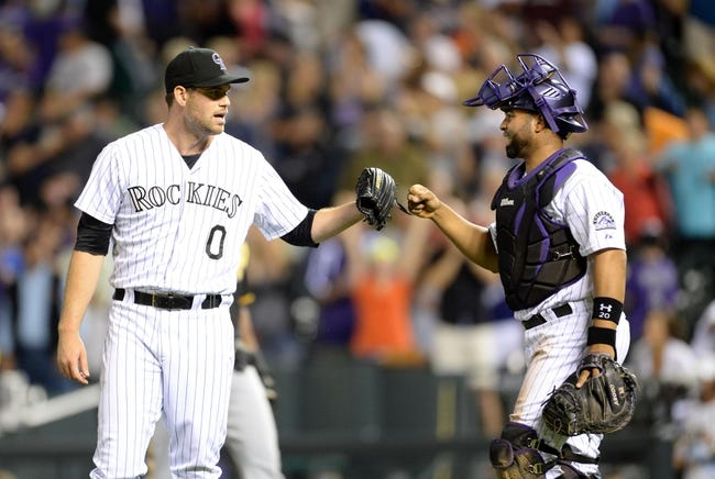 Jul 25, 2014; Denver, CO, USA; Colorado Rockies reliever Adam Ottavino (0) and catcher Wilin Rosario (20) react to the win over the Pittsburgh Pirates at Coors Field. The Rockies defeated the Pirates 8-1. Mandatory Credit: Ron Chenoy-USA TODAY Sports