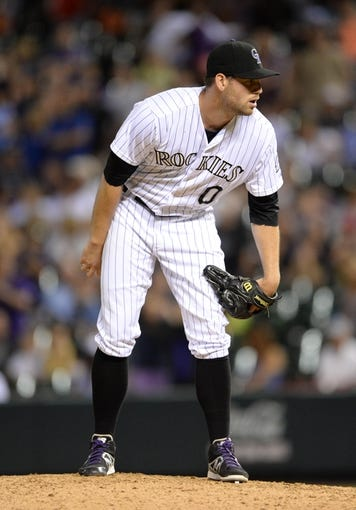Jul 25, 2014; Denver, CO, USA; Colorado Rockies reliever Adam Ottavino (0) prepares to deliver a pitch in the ninth inning against the Pittsburgh Pirates at Coors Field. The Rockies defeated the Pirates 8-1. Mandatory Credit: Ron Chenoy-USA TODAY Sports