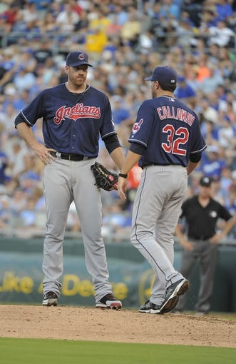 Jul 26, 2014; Kansas City, MO, USA; Cleveland Indians pitching coach Mickey Callaway (32) talks to starting pitcher Zach McAllister (34) in the fourth inning against the Kansas City Royals at Kauffman Stadium. Mandatory Credit: John Rieger-USA TODAY Sports