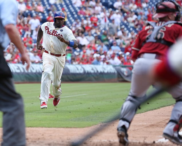 Jul 27, 2014; Philadelphia, PA, USA; Philadelphia Phillies first baseman Ryan Howard (6) rounds third and scores as Arizona Diamondbacks catcher Miguel Montero (26) is called for blocking the plate during the sixth inning at Citizens Bank Park. The Phillies won 4-2. Mandatory Credit: Bill Streicher-USA TODAY Sports