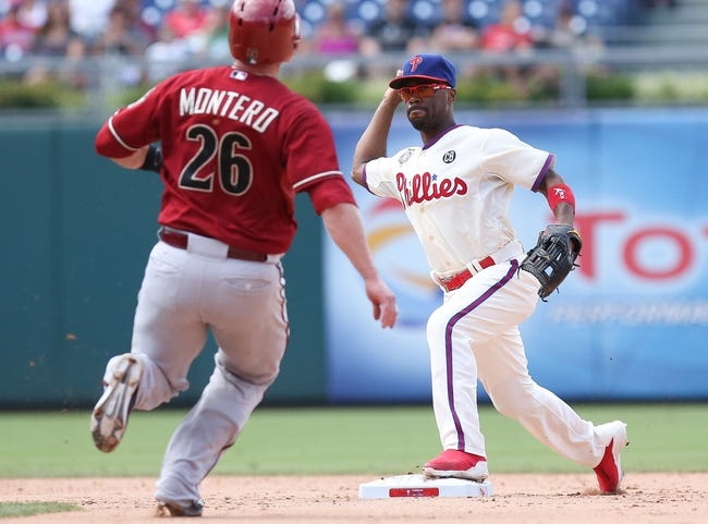 Jul 27, 2014; Philadelphia, PA, USA; Philadelphia Phillies shortstop Jimmy Rollins (11) turns a double play in front of the slide attempt of Arizona Diamondbacks catcher Miguel Montero (26) to end the game in the ninth inning at Citizens Bank Park. The Phillies won 4-2. Mandatory Credit: Bill Streicher-USA TODAY Sports
