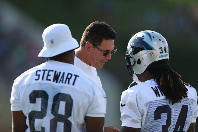 Jul 26, 2014; Spartanburg, SC, USA; Carolina Panthers head coach Ron Rivera talks with running back Jonathan Stewart (28) and running back DeAngelo Williams (34) during training camp at Gobbs Stadium. Mandatory Credit: Jim Dedmon-USA TODAY Sports
