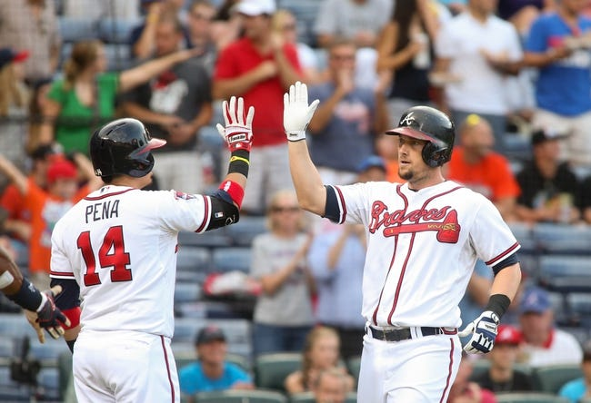 Jul 24, 2014; Atlanta, GA, USA; Atlanta Braves third baseman Chris Johnson (23) celebrates his two-run home run off of Miami Marlins starting pitcher Henderson Alvarez (not pictured) with Atlanta Braves second baseman Ramiro Pena (14) in the second inning of their game at Turner Field. Marlins won 3-2. Mandatory Credit: Jason Getz-USA TODAY Sports