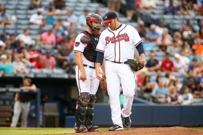 Jul 24, 2014; Atlanta, GA, USA; Atlanta Braves starting pitcher Aaron Harang (34) meets with Atlanta Braves catcher Evan Gattis (24) in the second inning of their game against the Miami Marlins at Turner Field. Marlins won 3-2. Mandatory Credit: Jason Getz-USA TODAY Sports