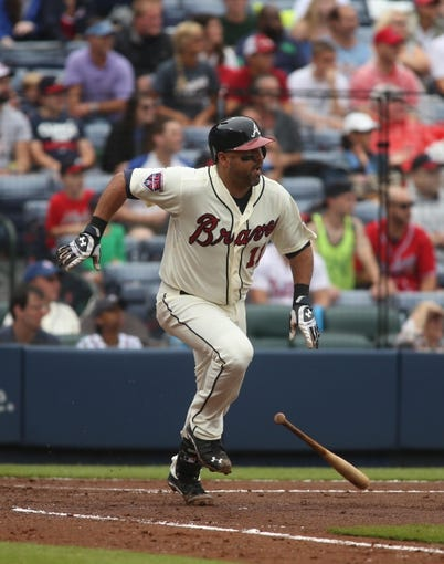 Jul 20, 2014; Atlanta, GA, USA; Atlanta Braves catcher Gerald Laird (11) hits a single in the second inning of their game against the Philadelphia Phillies at Turner Field. The Braves won 8-2. Mandatory Credit: Jason Getz-USA TODAY Sports