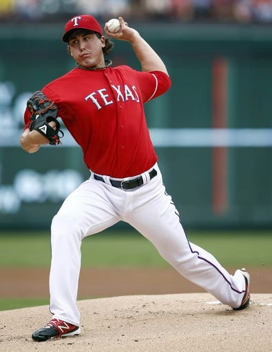 Sep 28, 2013; Arlington, TX, USA; Texas Rangers starting pitcher Derek Holland (45) delivers a pitch to the Los Angeles Angels during the first inning of a baseball game at Rangers Ballpark in Arlington. Mandatory Credit: Jim Cowsert-USA TODAY Sports