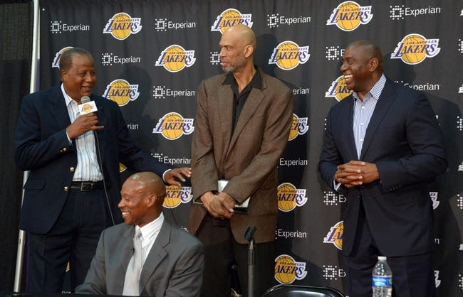 Jul 29, 2014; El Segundo, CA, USA; Jamaal Wilkes (left) speaks at a press conference to announce Byron Scott (second from left) as Los Angeles Lakers coach as Kareem Abdul-Jabbar (center) and Magic Johnson (right) listen at Toyota Sports Center. Mandatory Credit: Kirby Lee-USA TODAY Sports
