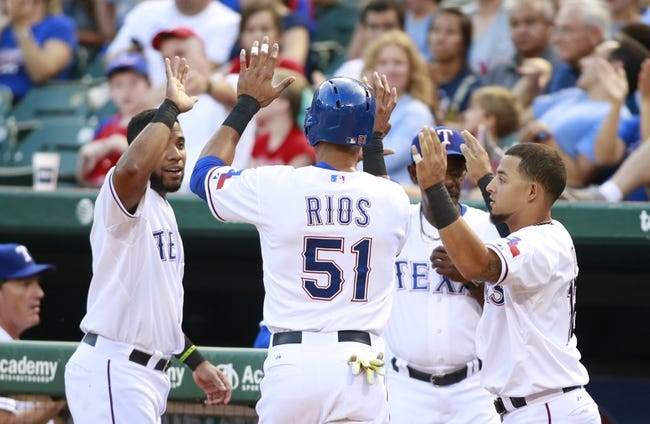 Jul 29, 2014; Arlington, TX, USA; Texas Rangers right fielder Alex Rios (51) is congratulated by shortstop Elvis Andrus (1) and second baseman Rougned Odor (12) after scoring a run in the third inning against the New York Yankees at Globe Life Park in Arlington. Mandatory Credit: Tim Heitman-USA TODAY Sports