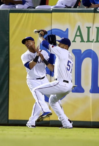 Jul 29, 2014; Arlington, TX, USA; Texas Rangers right fielder Alex Rios (51) is charged with an error after colliding with Texas Rangers center fielder Leonys Martin (2) in the sixth inning on a ball hit by New York Yankees left fielder Brett Gardner (not pictured) at Globe Life Park in Arlington. Mandatory Credit: Tim Heitman-USA TODAY Sports