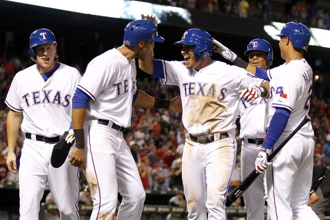 Jul 29, 2014; Arlington, TX, USA; Texas Rangers first baseman J.P. Arencibia (7) is congratulated by his teammates after hitting a grand slam home run in the seventh inning against the New York Yankees at Globe Life Park in Arlington.  New York beat Texas 12-11. Mandatory Credit: Tim Heitman-USA TODAY Sports
