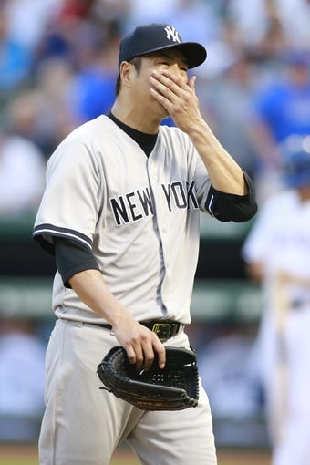 Jul 30, 2014; Arlington, TX, USA; New York Yankees starting pitcher Hiroki Kuroda (18) walks off the mound after the first inning against the Texas Rangers at Globe Life Park in Arlington. Mandatory Credit: Tim Heitman-USA TODAY Sports