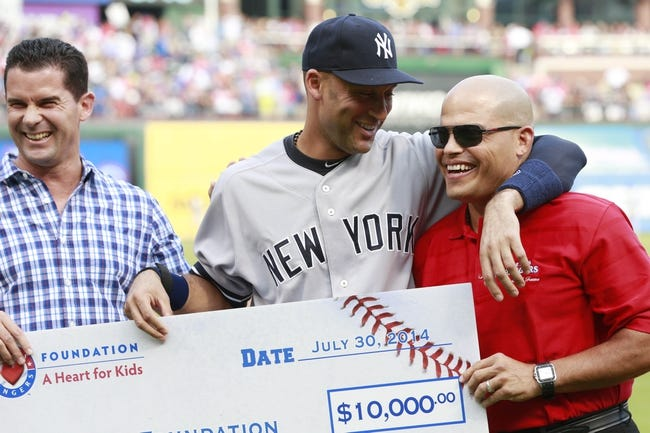 Jul 30, 2014; Arlington, TX, USA; Texas Rangers former second baseman Michael Young (L), New York Yankees shortstop Derek Jeter (2) and Texas Rangers former catcher Ivan Rodriguez (R) pose with a $10,000 check for the Turn 2 Foundation during a pre-game ceremony at Globe Life Park in Arlington. Mandatory Credit: Tim Heitman-USA TODAY Sports