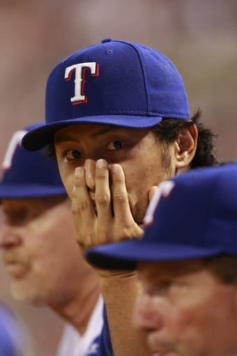 Jul 30, 2014; Arlington, TX, USA; Texas Rangers starting pitcher Yu Darvish (11) watches the game against the New York Yankees at Globe Life Park in Arlington.  Texas beat New York 3-2. Mandatory Credit: Tim Heitman-USA TODAY Sports