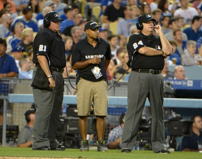 Jul 30, 2014; Los Angeles, CA, USA; Home plate umpire Hunter Wendelstedt (21) and second base umpire Jerry Layne (24) and replay technician Kien Milledge (center) during a video review of a play in the third inning of the game between the Atlanta Braves and the Los Angeles Dodgers at Dodger Stadium. Mandatory Credit: Kirby Lee-USA TODAY Sports
