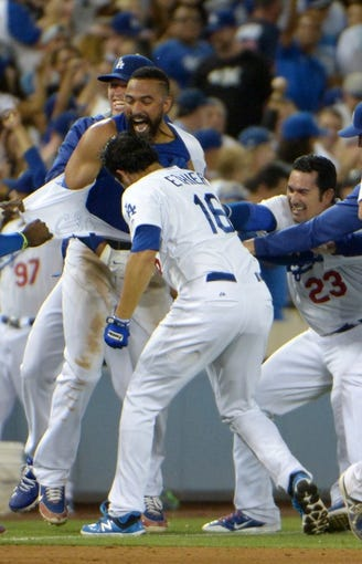 Jul 30, 2014; Los Angeles, CA, USA; Los Angeles Dodgers center fielder Matt Kemp (center) with teammates Andre Ethier (16) and Adrian Gonzalez (23) after hitting a walk-ff single in the 10th inning against the Atlanta Braves at Dodger Stadium. The Dodgers defeated the Braves 2-1 in 10 innings. Mandatory Credit: Kirby Lee-USA TODAY Sports