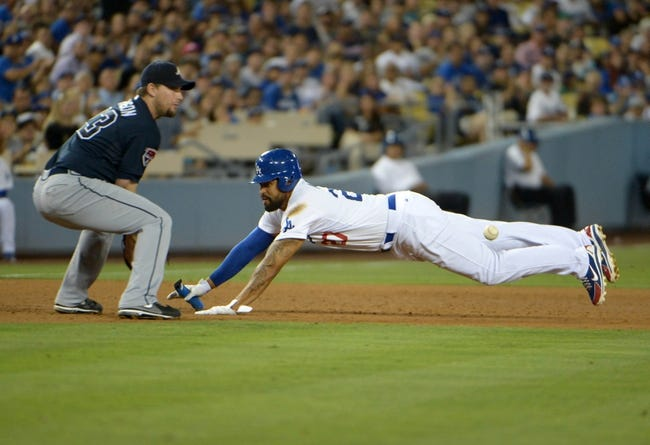 Jul 30, 2014; Los Angeles, CA, USA; Los Angeles Dodgers right fielder Matt Kemp (27) slides third base to beat a throw to Atlanta Braves third baseman Chris Johnson to at Dodger Stadium. The Dodgers defeated the Braves 2-1 in 10 innings. Mandatory Credit: Kirby Lee-USA TODAY Sports