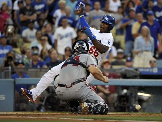 Jul 31, 2014; Los Angeles, CA, USA;  Los Angeles Dodgers right fielder Yasiel Puig (66) scores on a first baseman Adrian Gonzalez (not pictured) double in the 1st inning against the Atlanta Braves at Dodger Stadium. Atlanta Braves catcher Evan Gattis (24) tries to apply the tag. Mandatory Credit: Robert Hanashiro-USA TODAY Sports