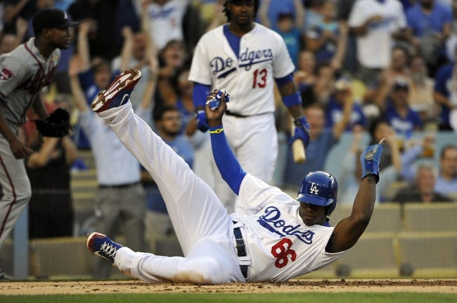 Jul 31, 2014; Los Angeles, CA, USA;  Los Angeles Dodgers right fielder Yasiel Puig (66) slides across home plate after scoring on a first baseman Adrian Gonzalez (not pictured) 1st inning double in the 1st inning against the Atlanta Braves at Dodger Stadium. Mandatory Credit: Robert Hanashiro-USA TODAY Sports