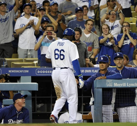Jul 31, 2014; Los Angeles, CA, USA; Los Angeles Dodgers right fielder Yasiel Puig (66) is greeted by manager Don Mattingly (8) at the dugout steps after hitting a solo home run in the 3rd inning against the Atlanta Braves at Dodger Stadium. Mandatory Credit: Robert Hanashiro-USA TODAY Sports