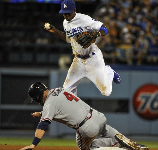 Jul 31, 2014; Los Angeles, CA, USA; Los Angeles Dodgers second baseman Dee Gordon (9) leaps out of the way of the sliding Atlanta Braves left fielder Ryan Doumit (4) on a force play at 2nd base in the 5th inning at Dodger Stadium. Mandatory Credit: Robert Hanashiro-USA TODAY Sports