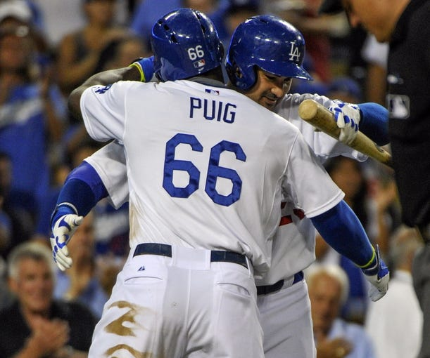 Jul 31, 2014; Los Angeles, CA, USA; Los Angeles Dodgers right fielder Yasiel Puig (66) is hugged by teammate first baseman Adrian Gonzalez (23) after hitting a solo home run in the 3rd inning against the Atlanta Braves at Dodger Stadium. Mandatory Credit: Robert Hanashiro-USA TODAY Sports