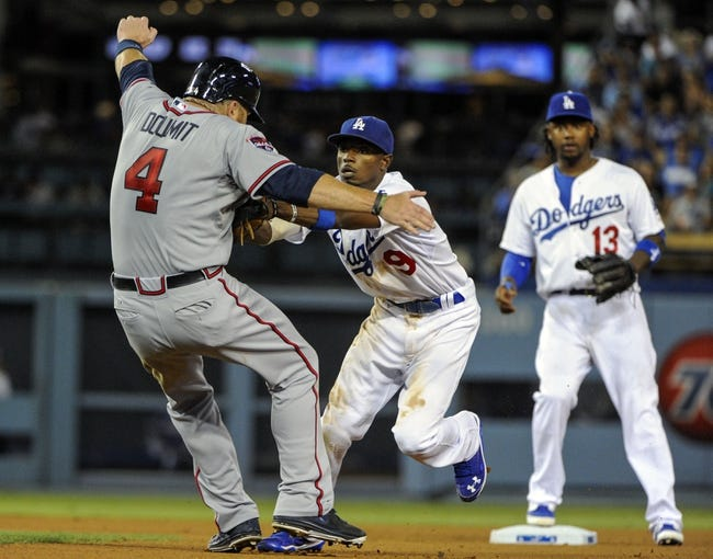 Jul 31, 2014; Los Angeles, CA, USA;Los Angeles Dodgers second baseman Dee Gordon (9) tags out Atlanta Braves left fielder Ryan Doumit (4) in the 8th inning to start a double play  at Dodger Stadium. Mandatory Credit: Robert Hanashiro-USA TODAY Sports