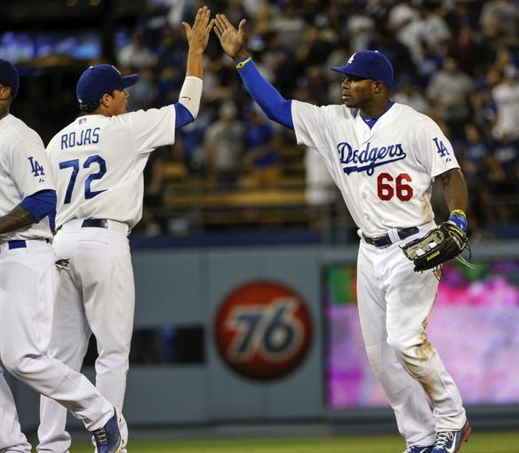 Jul 31, 2014; Los Angeles, CA, USA; Los Angeles Dodgers right fielder Yasiel Puig (66) high-fives shortstop Miguel Rojas (72) at the conclusion of the Dodgers 2-1 win over the Atlanta Braves at Dodger Stadium. The Dodgers won their 6th in a row in sweeping the Braves. Mandatory Credit: Robert Hanashiro-USA TODAY Sports
