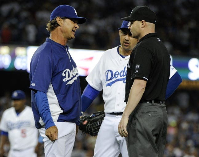 Jul 31, 2014; Los Angeles, CA, USA; Los Angeles Dodgers manager Don Mattingly (8) argues a close play at 1st base with umpire Jeff Kellogg (8) in the bottom of the 9th inning against the Atlanta Braves at Dodger Stadium. The play stood and the Braves runner was called safe. Los Angeles Dodgers first baseman Adrian Gonzalez (23) is in the middle. Mandatory Credit: Robert Hanashiro-USA TODAY Sports