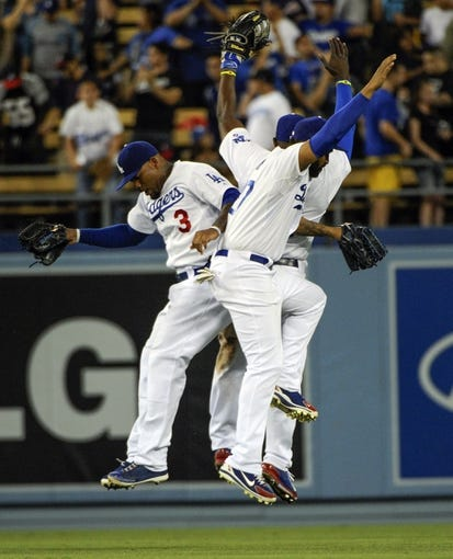Jul 31, 2014; Los Angeles, CA, USA; Los Angeles Dodgers left fielder Carl Crawford (3), right fielder Yasiel Puig (back) and right fielder Matt Kemp celebrate at the conclusion of the Dodgers 2-1 win over the Atlanta Braves at Dodger Stadium. The Dodgers swept the Braves in the 3-game series and have won 6 in a row. Mandatory Credit: Robert Hanashiro-USA TODAY Sports