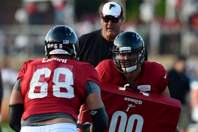 Aug 1, 2014; Lawrenceville, GA, USA; Atlanta Falcons guard Gabe Carimi (68) and offensive tackle Jake Matthews (70) work on a drill watched by offensive line coach Mike Tice (hat) during practice during Falcons Friday Night Lights at Archer High School. Mandatory Credit: Dale Zanine-USA TODAY Sports