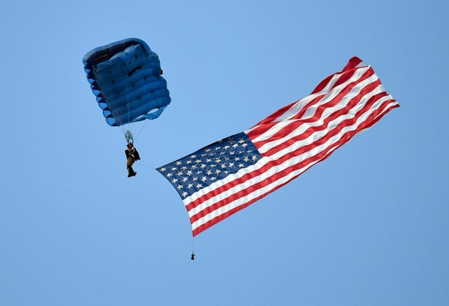 Aug 1, 2014; Lawrenceville, GA, USA; A skydiver brings the American flag to the field during Atlanta Falcons practice during Falcons Friday Night Lights at Archer High School. Mandatory Credit: Dale Zanine-USA TODAY Sports