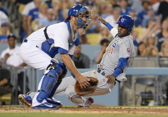 Aug 2, 2014; Los Angeles, CA, USA;  Chicago Cubs left fielder Junior Lake (21) beats the throw to Los Angeles Dodgers catcher Drew Butera (31) to score a run in the seventh inning of the game at Dodger Stadium. Mandatory Credit: Jayne Kamin-Oncea-USA TODAY Sports