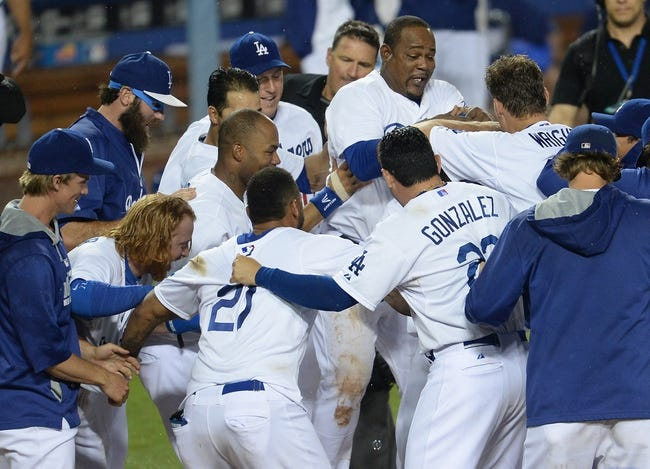 Aug 2, 2014; Los Angeles, CA, USA;  Los Angeles Dodgers shortstop Hanley Ramirez (13) is mobbed by teammates at home plate after a walk off 3-run home run in the twelfth inning of the game against the Chicago Cubs at Dodger Stadium. Dodgers won 5-2. Mandatory Credit: Jayne Kamin-Oncea-USA TODAY Sports