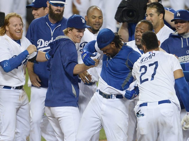 Aug 2, 2014; Los Angeles, CA, USA;  Los Angeles Dodgers shortstop Hanley Ramirez (middle) gets his jersey ripped off by teammates after hitting a walk off 3-run home run in the twelfth inning of the game against the Chicago Cubs at Dodger Stadium. Dodgers won 5-2. Mandatory Credit: Jayne Kamin-Oncea-USA TODAY Sports