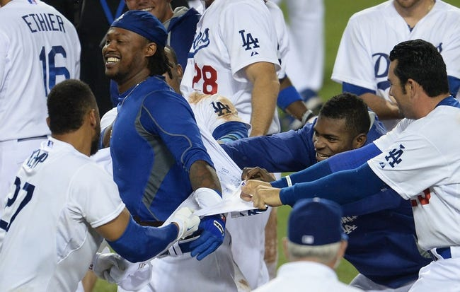Aug 2, 2014; Los Angeles, CA, USA;  Los Angeles Dodgers shortstop Hanley Ramirez (second from left) gets his jersey ripped off by teammates after hitting a walk off 3-run home run in the twelfth inning of the game against the Chicago Cubs at Dodger Stadium. Dodgers won 5-2. Mandatory Credit: Jayne Kamin-Oncea-USA TODAY Sports