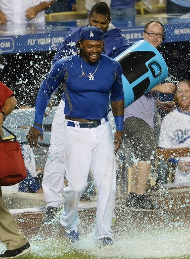 Aug 2, 2014; Los Angeles, CA, USA;  Los Angeles Dodgers center fielder Yasiel Puig (rear) pours a bucket of Powerade over shortstop Hanley Ramirez after Ramirez hit a walk off 3-run home run in the twelfth inning of the game against the Chicago Cubs at Dodger Stadium. Dodgers won 5-2. Mandatory Credit: Jayne Kamin-Oncea-USA TODAY Sports
