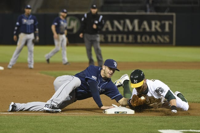 August 4, 2014; Oakland, CA, USA; Oakland Athletics second baseman Eric Sogard (28, right) advances to third base safely against Tampa Bay Rays third baseman Evan Longoria (3, left) during the fourth inning at O.co Coliseum. Mandatory Credit: Kyle Terada-USA TODAY Sports