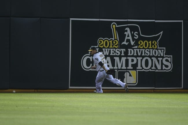 August 4, 2014; Oakland, CA, USA; Oakland Athletics left fielder Brandon Moss (37) chases a baseball on a triple by Tampa Bay Rays right fielder Kevin Kiermaier (39, not pictured) during the fifth inning at O.co Coliseum. Mandatory Credit: Kyle Terada-USA TODAY Sports