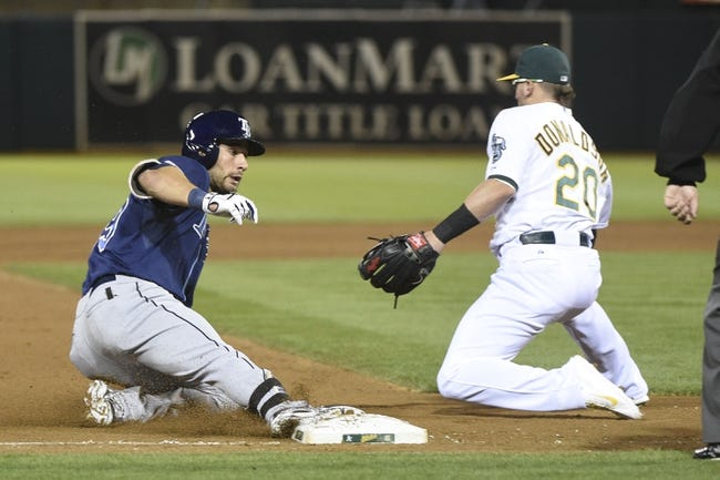 August 4, 2014; Oakland, CA, USA; Tampa Bay Rays right fielder Kevin Kiermaier (39, left) slides safely into third base for a triple against Oakland Athletics third baseman Josh Donaldson (20) during the fifth inning at O.co Coliseum. Mandatory Credit: Kyle Terada-USA TODAY Sports