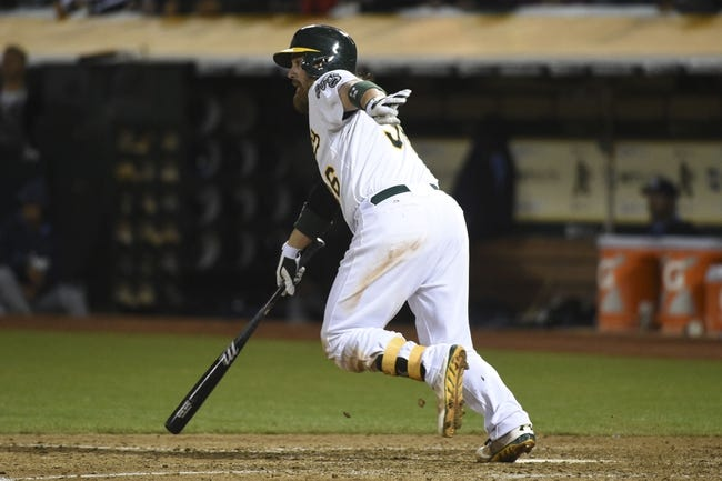 August 4, 2014; Oakland, CA, USA; Oakland Athletics catcher Derek Norris (36) hits a game-winning RBI-single scoring center fielder Sam Fuld (23, not pictured) against the Tampa Bay Rays during the tenth inning at O.co Coliseum. The Athletics defeated the Rays 3-2. Mandatory Credit: Kyle Terada-USA TODAY Sports
