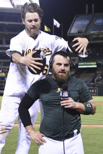 August 4, 2014; Oakland, CA, USA; Oakland Athletics right fielder Josh Reddick (16, top) pies catcher Derek Norris (36, bottom) after Norris hit the game-winning RBI-single during the 10th inning against the Tampa Bay Rays at O.co Coliseum. The Athletics defeated the Rays 3-2. Mandatory Credit: Kyle Terada-USA TODAY Sports