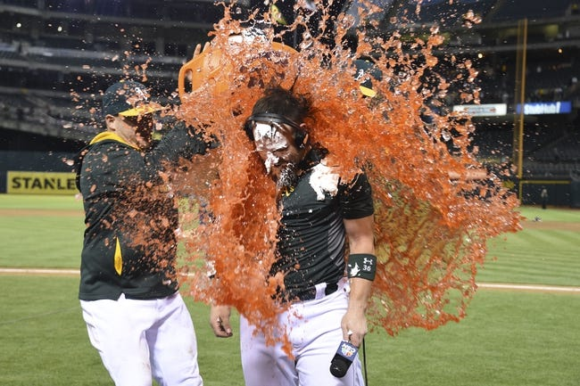 August 4, 2014; Oakland, CA, USA; Oakland Athletics first baseman Stephen Vogt (21, left) dumps Gatorade on catcher Derek Norris (36, right) after Norris hit the game-winning RBI-single during the 10th inning against the Tampa Bay Rays at O.co Coliseum. The Athletics defeated the Rays 3-2. Mandatory Credit: Kyle Terada-USA TODAY Sports