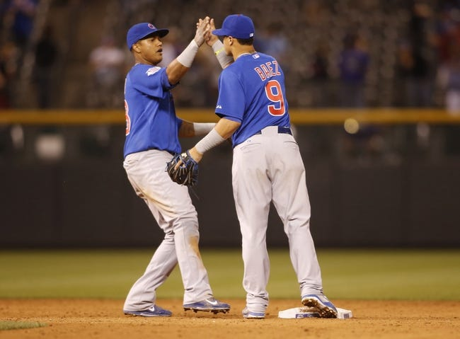 Aug 5, 2014; Denver, CO, USA; Chicago Cubs second baseman Javier Baez (9) and shortstop Starlin Castro (13) celebrate after the game against the Colorado Rockies at Coors Field. The Cubs won 6-5 in twelve innings.  Mandatory Credit: Chris Humphreys-USA TODAY Sports