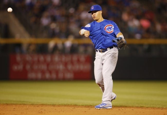 Aug 5, 2014; Denver, CO, USA; Chicago Cubs second baseman Javier Baez (9) fields a ground ball during the ninth inning against the Colorado Rockies at Coors Field. The Cubs won 6-5 in twelve innings.  Mandatory Credit: Chris Humphreys-USA TODAY Sports