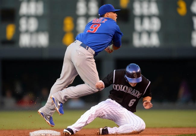 Aug 6, 2014; Denver, CO, USA; Chicago Cubs second baseman Javier Baez (9) turns a double play over Colorado Rockies left fielder Corey Dickerson (6) in the second inning at Coors Field. Mandatory Credit: Ron Chenoy-USA TODAY Sports