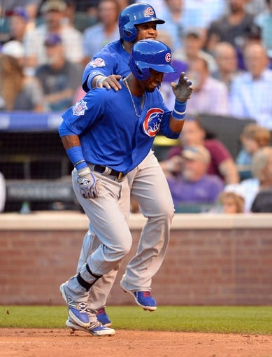 Aug 6, 2014; Denver, CO, USA; Chicago Cubs second baseman Arismendy Alcantara (7) and catcher Welington Castillo (5) celebrate scoring in the fourth inning against the Colorado Rockies at Coors Field. Mandatory Credit: Ron Chenoy-USA TODAY Sports