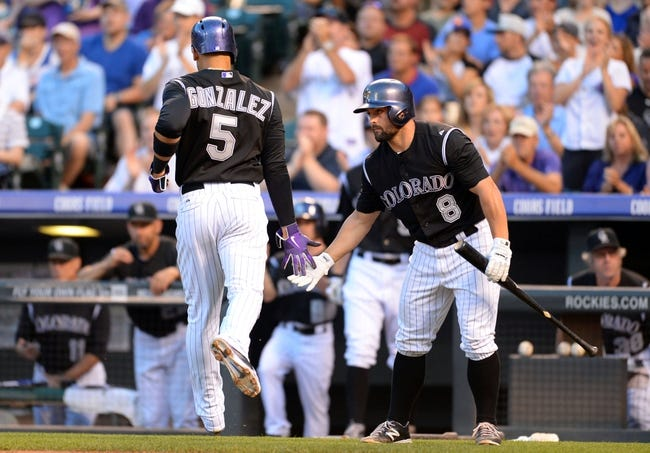 Aug 6, 2014; Denver, CO, USA; Colorado Rockies left fielder Carlos Gonzalez (5) is congratulated after scoring by catcher Michael McKenry (8) in the fourth inning against the Chicago Cubs at Coors Field. Mandatory Credit: Ron Chenoy-USA TODAY Sports